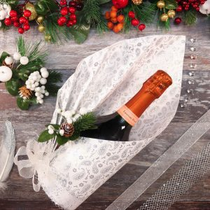 A fan pleated wrap, around a bottle of champagne finished with a pom pom bow, glitter ribbon and a white Christmas pick